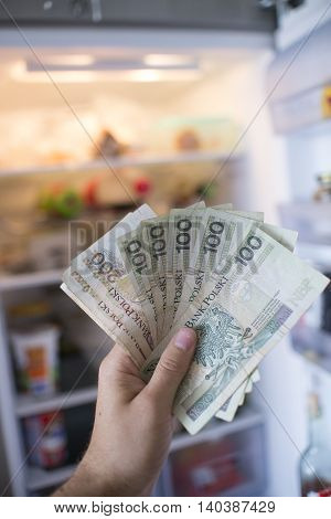 Hand With Pln  Money In Front Of Open Fridge