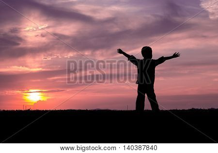 Sunset child silhouette with raised hands looking into the sun and dramatic sky with clouds. Concept of happiness, freedom, youth, timeless, serenity, comfort, joy, childhood memories.