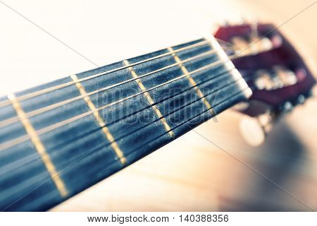Neck of a guitar with strings and head in the background. Musical instrument. Vintage colors. Shallow depth of field.