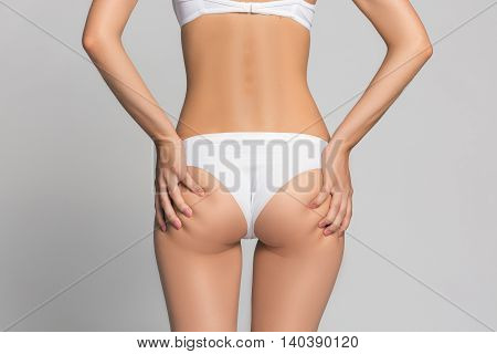 Young woman is touching her skin on buttock to check its supple. Isolated on gray. in white lingerie or underwear fashion and beauty spa massage