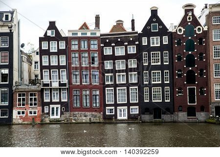 Panorama of a line of narrow old buildings in Amsterdam, Netherlands. The buildings are slanting and wedged together. The water of a canal is in the foreground.