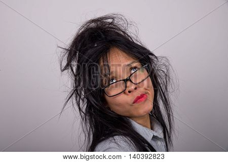 Crazy or frazzled looking Asian woman with bright lipstick and ruffled hair pulling a face while looking up.