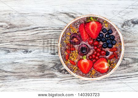 Acai breakfast superfoods smoothies bowl with chia seeds bee pollen goji berry toppings and peanut butter. Overhead top view.