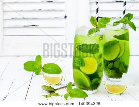 Matcha iced green tea with lime and fresh mint on white rustic background. Super food drink