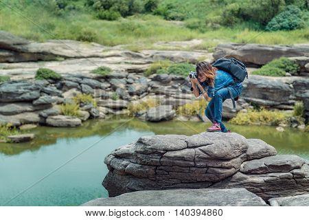 Asia woman taking a photo at Sampanbok natural stone park the grand-canyon of Ubonratchathani Thailand