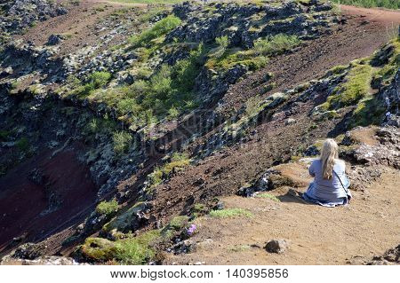 A single lady taking time to enjoy the wonders of a crater and its surroundings