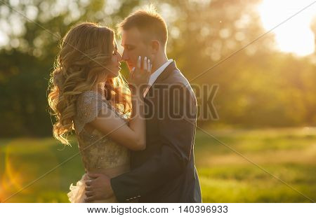 Young loving couple on the wedding day,the groom-a man with a short haircut,in a dark wedding suit and a beautiful bride-a woman with long curly hair in beige wedding dress standing arm in arm at sunset in summer green Park