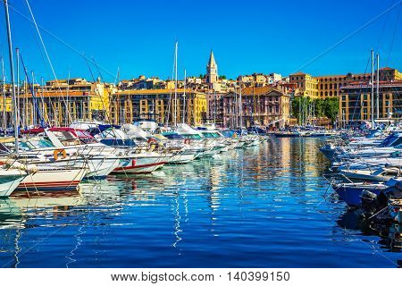 The blue water reflects the ancient buildings on the waterfront. Rows of sailing yachts, motor boats and fishing boats. The water area of Marseille Old Port