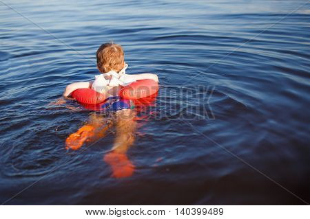 baby swims in the sea with inflatable circle. the boy wearing a modern neoprene shoes for swimming. baby swimming with a rubber circle for training swimmer. back view. empty space for your text