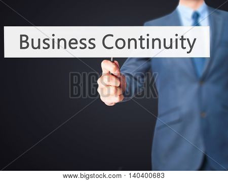 Business Continuity - Business Man Showing Sign