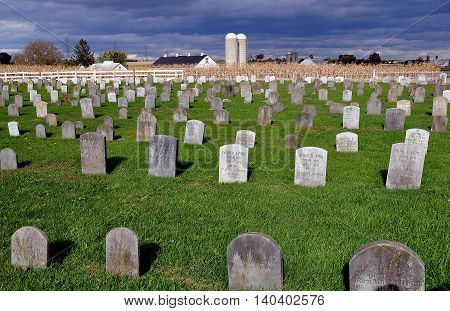 Lancaster County Pennsylvania - October 17 2015: Simple stone grave markers in an Amish burial ground with farm silos in the distance