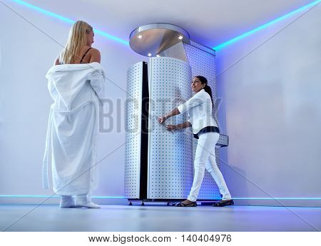Full length portrait of woman in bathrobe at cosmetology clinic going for cryotherapy treatment in cryosauna. Nurse standing at the door of freezing capsule. poster