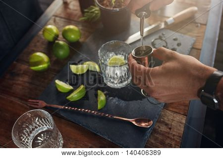 Pouring Alcohol In Jigger To Prepare A Cocktail
