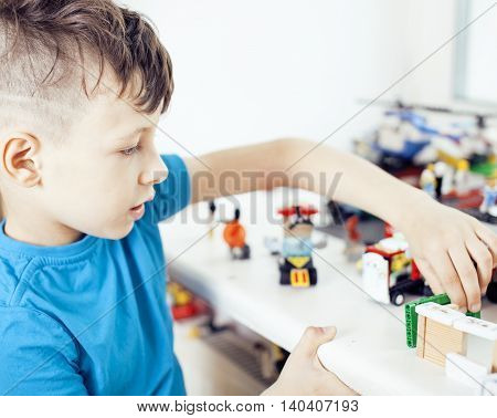 little cute preschooler boy playing lego toys at home happy smiling, lifestyle children concept poster