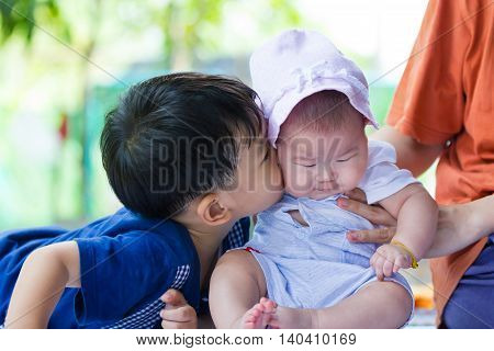 Closeup children having happy together brother kissing his sister. Conceptual image about loving and bonding of sibling. Happy family spending time together.