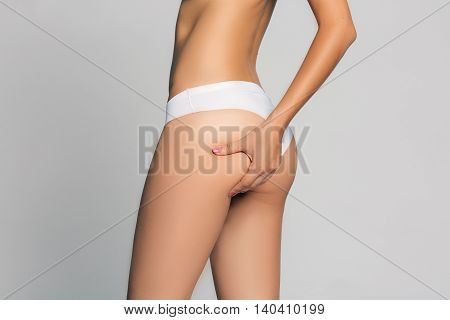 Young woman is touching her skin on buttock to check its supple. Isolated on white.