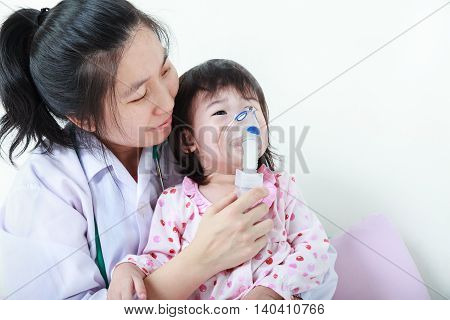 Asian Child Having Respiratory Illness Helped By Health Professional With Inhaler. Sad Girl Crying.