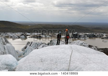 Photo of two ladies overlooking a glaicer lake from the smmitt