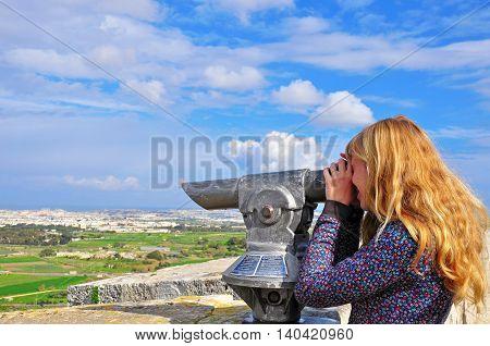 Blondy long-hair girl looking in telescope. Maltese Islands