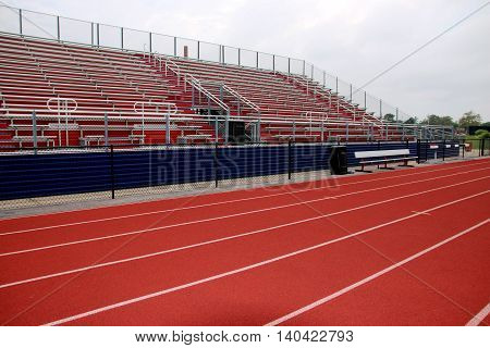 Lanes on a track in front of red and white bleachers,