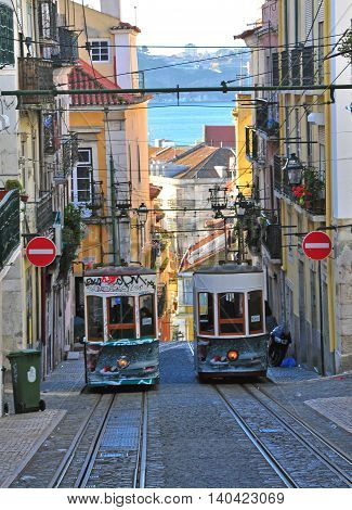 LISBON PORTUGAL - DECEMBER 28: Old funiculars goes by the street in Lisbon district Bairro Alto on december 28 2013. Lisbon transport system has three funiculars routes.