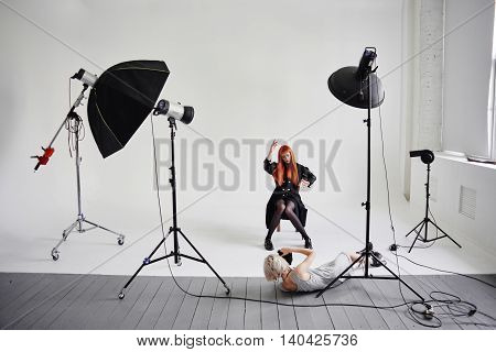 Girl photographer lies on the floor and shoots of fashion model posing on chair on white background in Studio