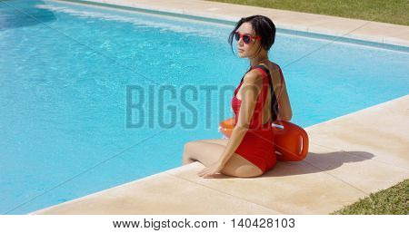 Watchful lifeguard sitting at side of pool