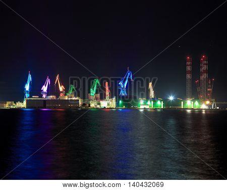Colorful Lighting Cranes in Pula, Istria, Croatia. Shipyard Uljanik. One of the City's Symbols. Night Photo with Reflection.