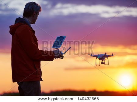 Man operating drone flying or hovering by remote control in sunset.