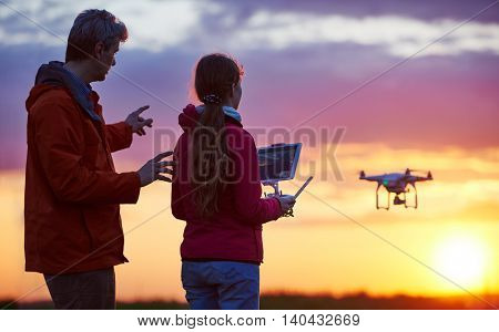 Man with child operating drone flying or hovering by remote control in sunset.