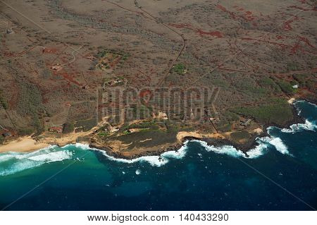 Aerial of Northwest coast beach of Molokai with waves crashing into shore and surrounding area of island with roads homes but largely undeveloped. April 2016.