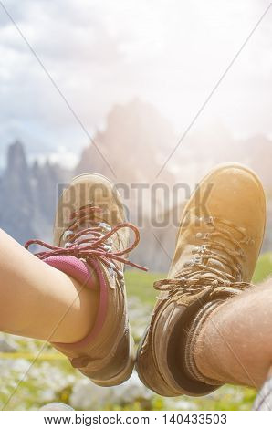 Man hiker lie on a ground. Peaks like a background. Sunny day.Trekking boots.Lens flare. Succesful backpacker enjoy a view.