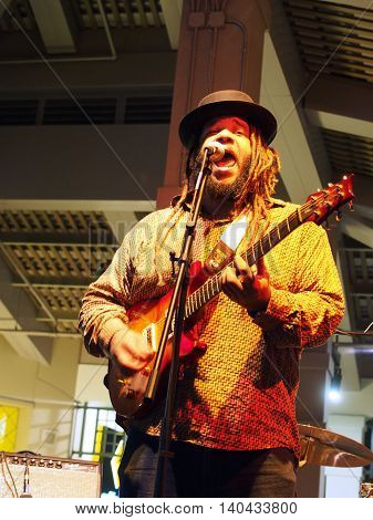 HONOLULU HI - JANUARY 29: Lead singer of Guidance Band plays guitar and sings as he Jams on stage at Mai Tai Bar in Ala Moana Shopping Center on January 29 2016 Honolulu Hawaii.