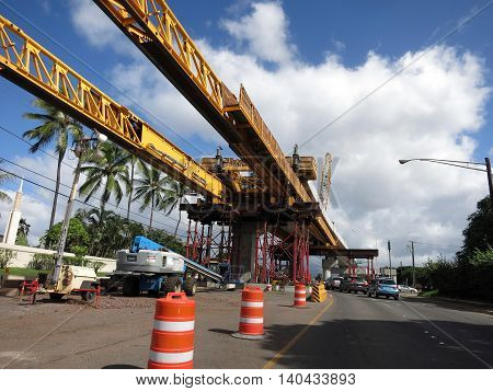 HONOLULU - NOVEMBER 29: HART Light Rail concrete guideway under construction in road center with machines in Pearlrigde on Oahu Hawaii on November 29 2015. HART is building a 8 billlion dollar railway linking Oahu communities.