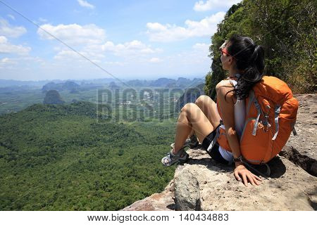 young woman backpacker hiking on mountain peak rock