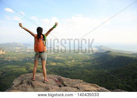 successful woman hiker enjoy the view at sunrise mountain peak