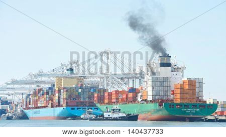 Oakland CA - July 27 2016: Cargo Ships today are significantly larger than their predecessors and are unable to maneuver sideways. Tugboats push SEASPAN CHIWAN sideways to the dock at the Port of Oakland.