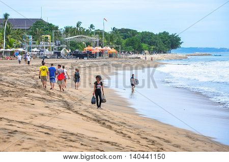 Bali,Indonesia-May 28,2010:Foreign tourists walk along Kuta beach at Bali,Indonesia,also known as Sunset Beach or Sanur Beach.Luxury resorts,restaurants & clubs are located along the beach.