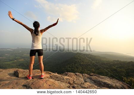 young successful woman open arms on mountain peak