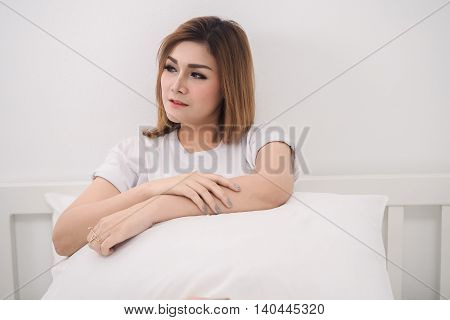 pretty woman hugging white pillow on bed and looking something in bedroom lonely concept.