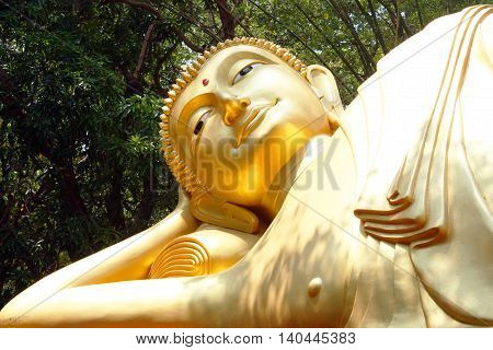 The face of Reclining Buddha image The attitude of Nirvana peaceful exquisite Buddha statue religious.