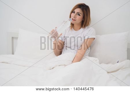 Asian woman drinking water on white bed in the morning Healthy lifestyle concept.