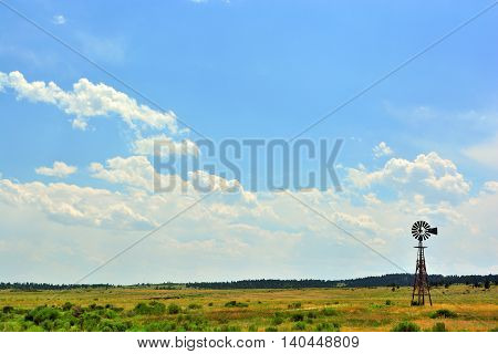Rural Ranch Prairie Field with an Antique Windmill and Puffy White Clouds