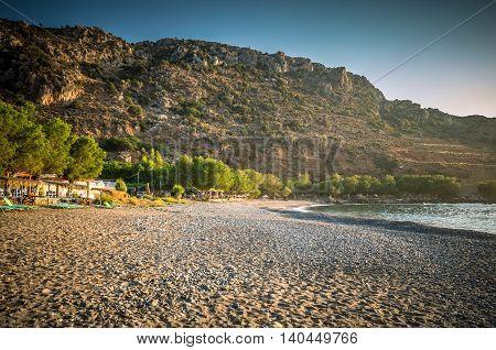 Sfinari Beach in Crete island, Greece. Straw parasols and sunbeds on the beach in twilight. poster