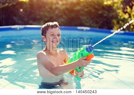 Happy little boy laugh and shoot with squirt gun in sunset