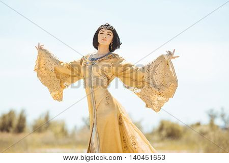 Fashion stylish beauty woman with black short haircut and professional make-up of Cleopatra. Girl standing in golden dress outdoors in desert. Hot sunny weather