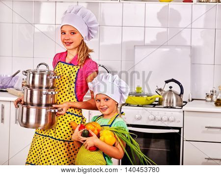 Children wearing cooking hat and cooking apron are cooking at kitchen.