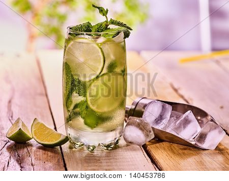 On wooden boards is high glass with alcohol drink and ice cubes. Drink two hundred ninety-three cocktail mohito and scoop ice . Country life high cocktail with mint sprig . Outdoor. Light background.
