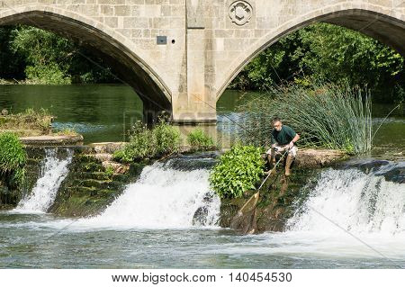 BATH UK - JULY 29 2016 Fisherman on Bathampton Weir with rod and net. Amateur angler scoops fish into net on waterfall in River Avon on a sunny summer afternoon