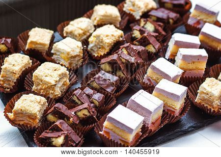 Beautifully decorated catering banquet table with different food snacks, appetizers with assortment of sweets on corporate christmas birthday kids party event or wedding celebration. Background food.